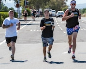 """Eric Silva, a track and field athlete competing in the Special Olympics, runs with police officers from the Fairfield Police Department to deliver """"The Flame of Hope"""" Special Olympics Torch to Travis Air Force Base, Calif., June 21, 2017. The torch run brings local law enforcement together from Solano County to show their support for the Special Olympics. (U.S. Air Force photo by Louis Briscese)"""