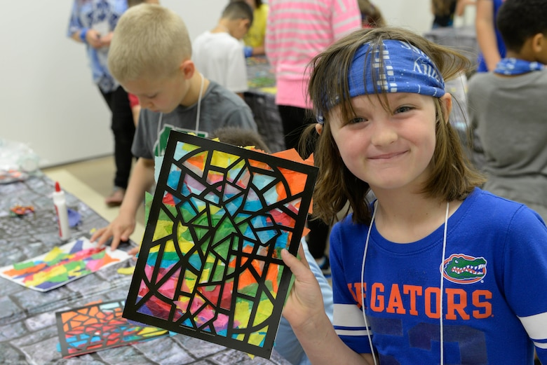A child poses with her stained glass window artwork at Yokota Air Base, Japan, June 23, 2017. A different story from the Bible served as the theme for the activities each day.
