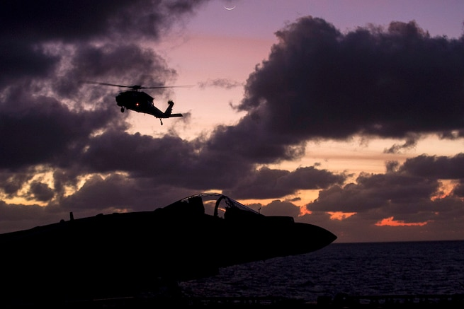 A Navy MH-60S Seahawk helicopter approaches the starboard side of the USS Bonhomme Richard during fast-rope training in the Pacific Ocean during low light, June 25, 2017. Marine Corps photo by Staff Sgt. T. T. Parish