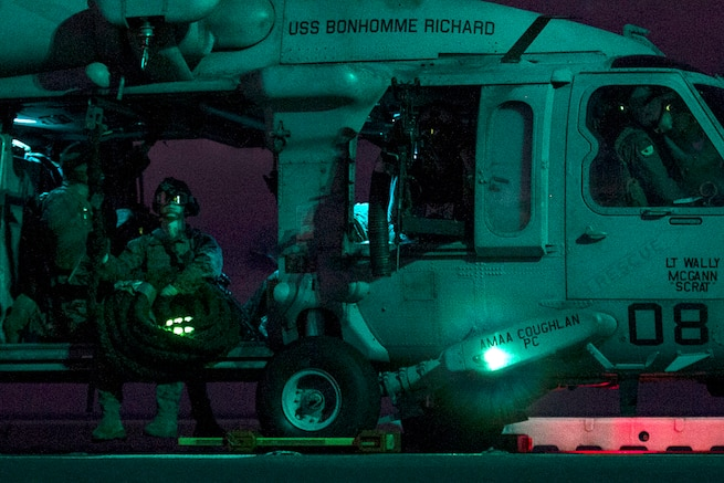 Marines sit inside a Navy MH-60S Seahawk helicopter before takeoff during fast-rope training aboard the USS Bonhomme Richard in the Pacific Ocean during low light, June 25, 2017. Marine Corps photo by Staff Sgt. T. T. Parish