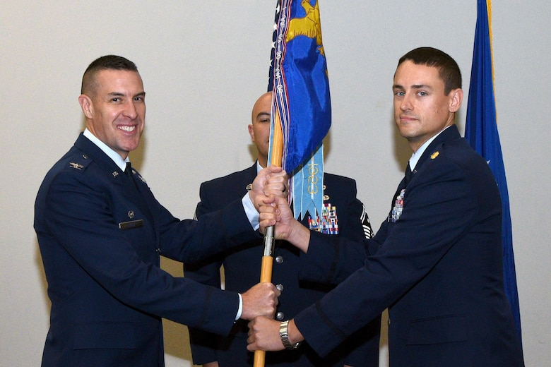 U.S. Air Force Maj. Curtis Shwarz, the new 17th Logistics Readiness Squadron Commander, receives the unit guideon from Col. Jason Beck, 17th Missions Support Group Commander, during the 17th LRS Change of Command ceremony at the Event Center on Goodfellow Air Force Base, Texas, June 27, 2017. The passing of the guideon represents the formal exchange of command. (U.S. Air Force photo by Airman 1st Class Randall Moose/Released)