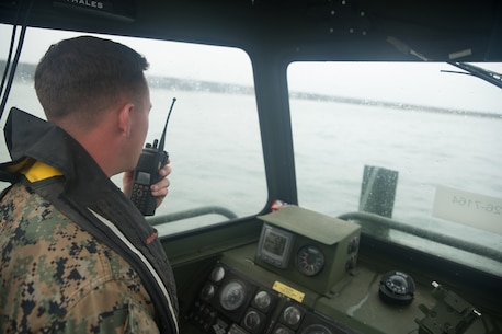 U.S. Marine Cpl. Braxton Shrader, a combat engineer with Bridge Company, 7th Engineer Support Battalion, 1st Marine Logistics Group communicates over the radio on a Bridge Erection Boat (BEB) during the boat licensing course along the coast of Camp Pendleton, Calif., June 21, 2017. The BEB deploys improved ribbon bridges, which are long two-way platforms used to transport heavy equipment, such as tanks, over bodies of water. (U.S. Marine Corps photo by Lance Cpl. Timothy Shoemaker)