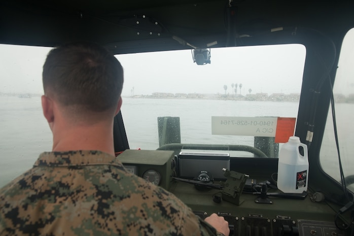 U.S. Marine Cpl. Braxton Shrader, a combat engineer with Bridge Company, 7th Engineer Support Battalion, 1st Marine Logistics Group observes his surroundings while on the Bridge Erection Boat (BEB) during a boat licensing course along the coast of Camp Pendleton, Calif., June 21, 2017. The BEB deploys improved ribbon bridges, which are long two-way platforms used to transport heavy equipment, such as tanks, over bodies of water. (U.S. Marine Corps photo by Lance Cpl. Timothy Shoemaker)