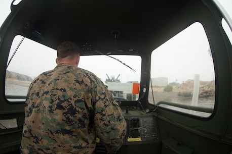 U.S. Marine Cpl. Braxton Shrader, a combat engineer with Bridge Company, 7th Engineer Support Battalion, 1st Marine Logistics Group observes his surroundings while on the Bridge Erection Boat (BEB) during a boat licensing course along the coast of Camp Pendleton, Calif., June 21, 2017 The BEB deploys improved ribbon bridges, which are long two-way platforms used to transport heavy equipment, such as tanks, over bodies of water.  (U.S. Marine Corps photo by Lance Cpl. Timothy Shoemaker)