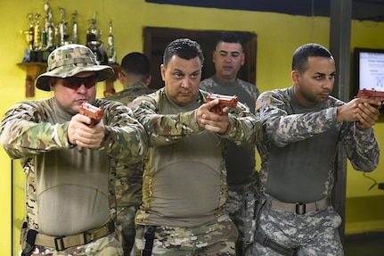 A team from Joint Task Force-Bravo's Joint Security Forces show local police forces how to group before entering a room for clearing at La Paz, Honduras so they can communicate with gestures and body movements when entering a room for clearing during a