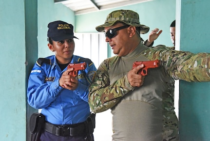 U.S. Army Staff Sgt. Marcos Dejesus, Joint Task Force-Bravo Joint Security Forces, explains tactical movements for clearing rooms to a local police officer at La Paz, Honduras, June 20, 2017.