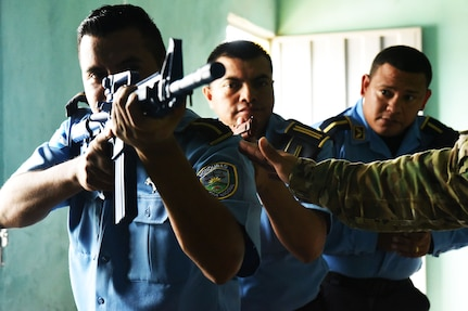 Honduran police forces prepare to enter a room for clearing under a hostile scenario during a Subject Matter Expert Exchange with Joint Security Forces from Joint Task Force-Bravo at La Paz, June 20, 2017.  The Military Police members shared knowledge on how to enter buildings and clear the areas tactically, providing the Honduran forces with necessary techniques and procedures that can help prevent casualties among their force while entering hostile situations.