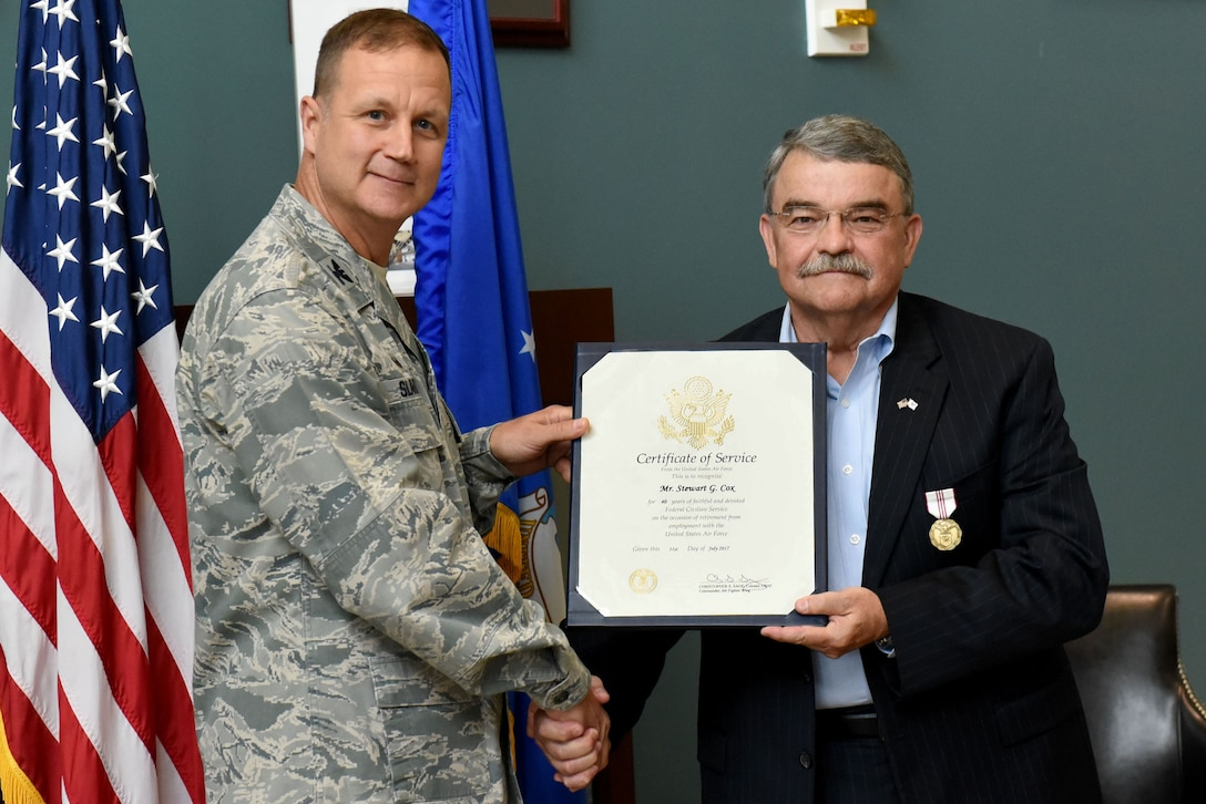 Col. Joseph P. Slavick, 4th Mission Support Group commander, presents Stewart G. Cox, 4th Mission Support Group civilian deputy commander, with a Certificate of Service, June 22, 2017, at Seymour Johnson Air Force Base, North Carolina. Cox retired after 40 years of service to the Air Force both on active duty and a civilian employee. (U.S. Air Force photo by Airman 1st Class Victoria Boyton)