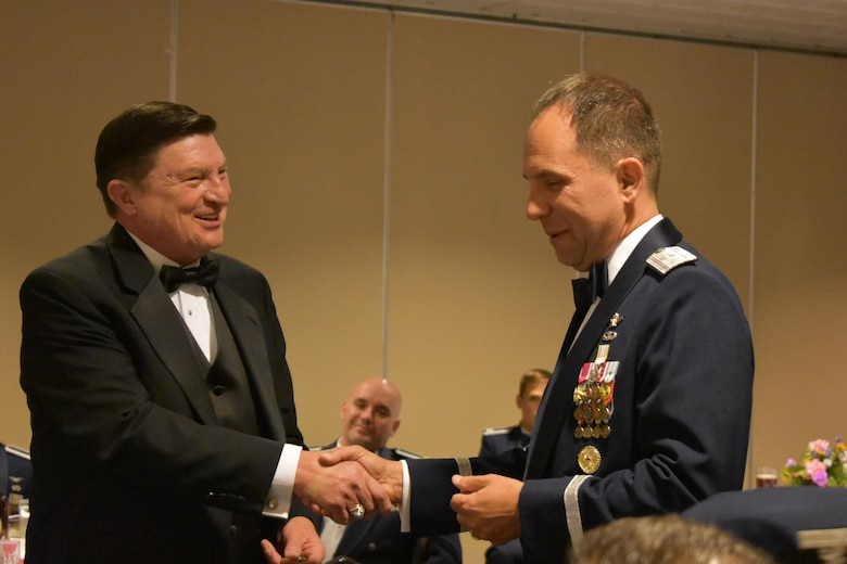 Brig. Gen. John Shaw (right), Air Force Space Command director of Strategic Plans, Programs, Requirements and Analysis, coins retired Col. Mason Beckett, former 25th Strategic Training Squadron (now 25th Space Range Squadron) commander, during the Centennial Dinner Banquet at Peterson Air Force Base, Colorado, Wednesday, June 22, 2017. Shaw presented Beckett with his coin after his speech. (U.S. Air Force photo/2nd Lt. Scarlett Rodriguez)