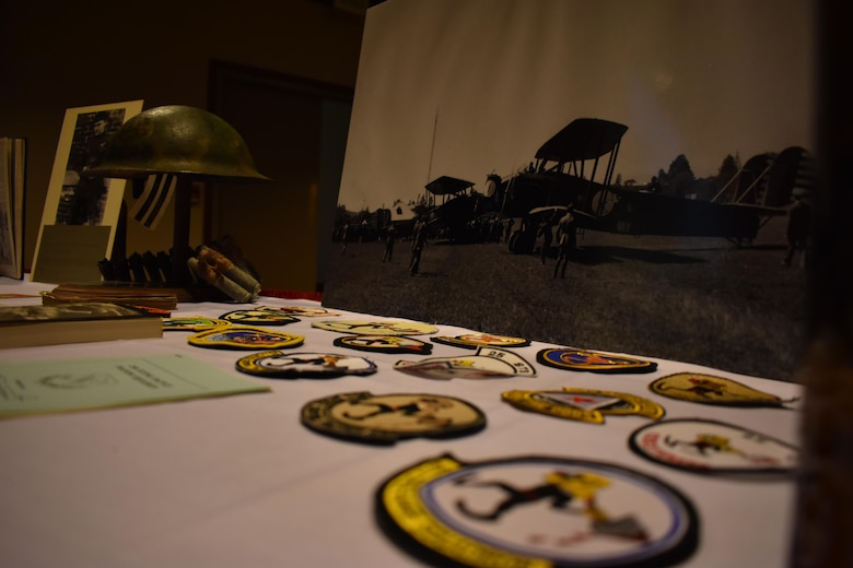 25th Space Rage Squadron artifacts dating back to World War I, along with years of squadron patches, lay out on display during the Centennial Dinnner Banquet at Peterson Air Force Base, Colorado, Wednesday, June 21, 2017. Before guests participated in the night's events, guests signed a large graphic as a memento of the centennial. (U.S. Air Force photo/2nd Lt. Scarlett Rodriguez)