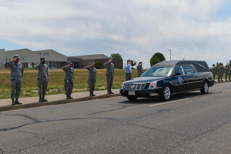 Members of Team Buckley render a final salute to Major Elgin Ross, Chief, Total Force Service Center, assigned to Headquarters Air Reserve Personnel Center, June 27, 2017, on Buckley Air Force Base, Colo. Ross tragically passed away after becoming unresponsive while conducting his physical training test on June 16. The Buckley community paid their last respects to Ross and his family at a funeral procession on Aspen Street, from the Mississippi Gate to the 6th Avenue Gate. (U.S. Air Force photo by Airman Jacob Deatherage/Released)