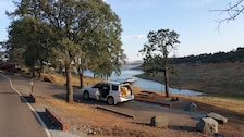 A camper settles in to a campsite with a nice lake view at New Hogan Lake.