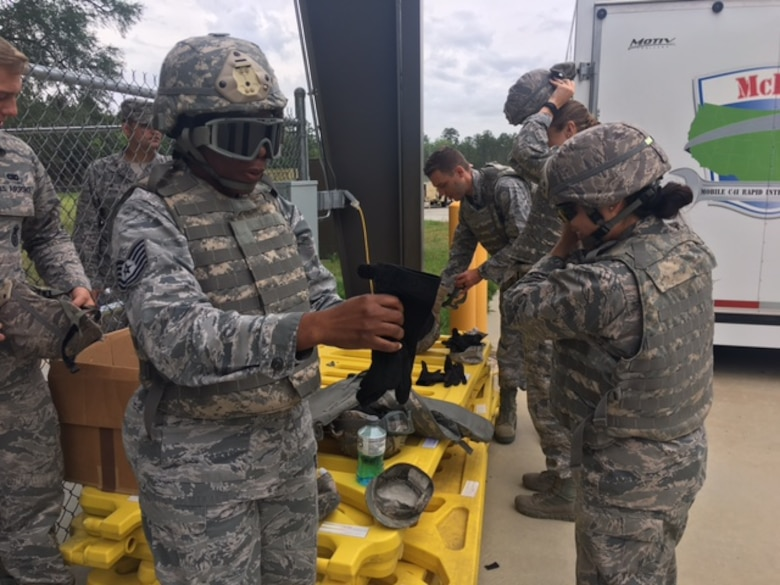 Class members from Emerge Moody put on protective gear prior to experiencing a Mine-Resistant Ambush Protected vehicle egress assistance trainer May 2, 2017, at Moody Air Force Base, Ga. Emerge Moody spent the day with the 820th BDG learning about the organization's mission and capabilities. (Courtesy Photo)