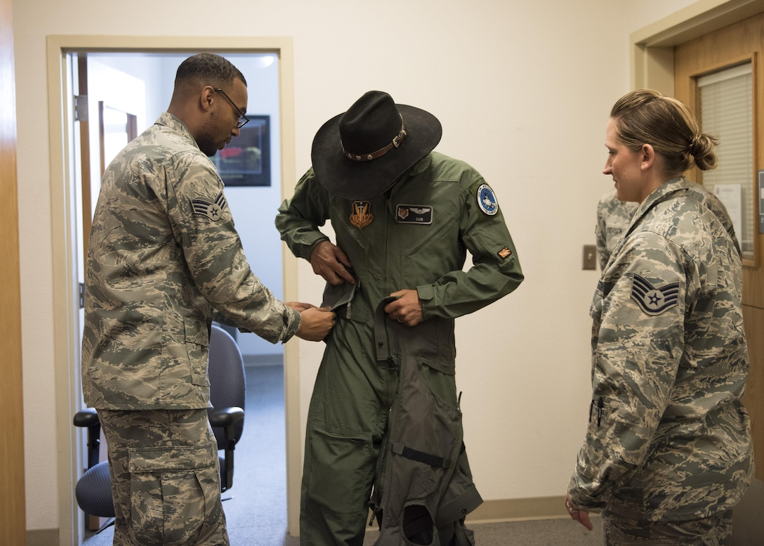 Senior Airman Quincy Neely-Lewis, 366th Operations Support Squadron aircrew flight equipment journeyman, helps prepare Vice Chairman Buster Gibson of the Shoshone-Paiute Tribes of the Duck Valley Indian Reservation for his orientation flight, June 16, 2017, at Mountain Home Air Force Base , Idaho. Aircrew Flight Equipment helps to ensure that all flight and safety equipment is in perfect working order. (U.S. Air Force photo by Airman 1st Class Alaysia Berry/Released)