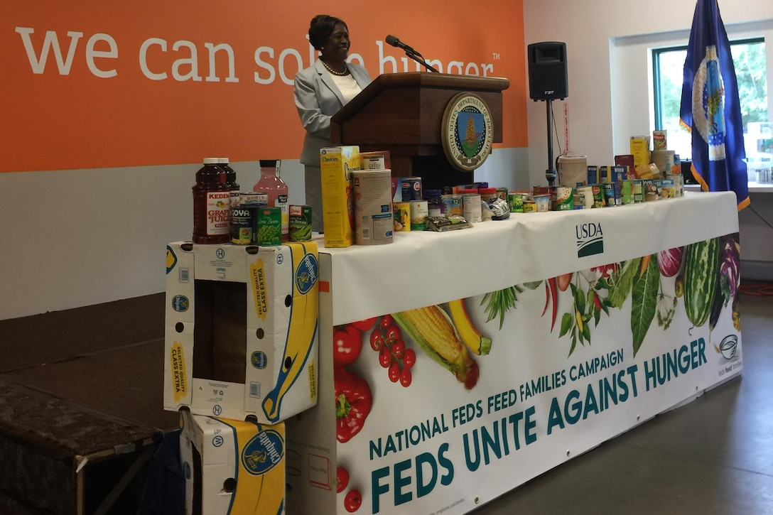This image shows a woman speaking at a podium behind a table of nonperishable food items.