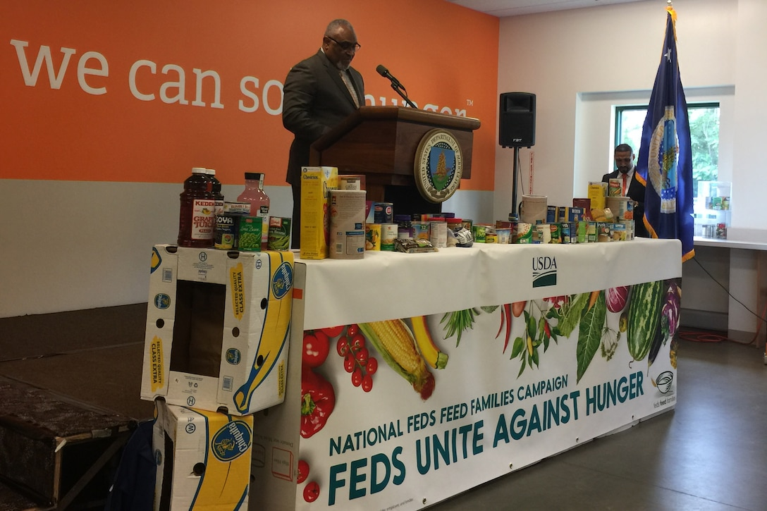This image shows a man speaking at a podium behind a table of nonperishable food items.