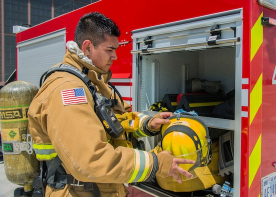 Airman 1st Class Macario Martinez, 375th CES fire fighter, grabs his helmet to participate in a training exercise at Scott Air Force Base, Ill. on June 22, 2017. The exercise was part of the unit's Airport Rescue and Fire Fighting's training which tests their ability to arrive on scene, fight fires, and provide a rescue path as well as recover or rescue personnel. (U.S. Air Force photo by Airman 1st Class Daniel Garcia)