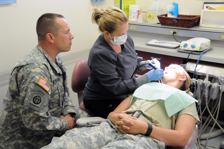 Sgt. Matthew Kunsch, a dental specialist assigned to 7406th Troop Medical Clinic located in Kansas City, Missouri, learns how to perform a general cleaning from staff member Michelle Scott, a dental hygienist on the team.  Kunsch is one of approximately 25 U.S. Army Reserve Soldiers who are working in partnership with Rosebud Indian Health Service to provide medical care to the local tribal population.