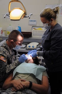 Sgt. Matthew Kunsch, a dental specialist assigned to 7406th Troop Medical Clinic located in Kansas City, Missouri, learns how to perform a general cleaning on fellow Soldier, Sgt. Jennifer Kunsch, from staff member Michelle Scott, a dental hygienist on the team.  Both Matthew and Jennifer are  part of a small medical team of approximately 25 U.S. Army Reserve Soldiers who are working in partnership with Rosebud Indian Health Service to provide medical care to the local tribal population.