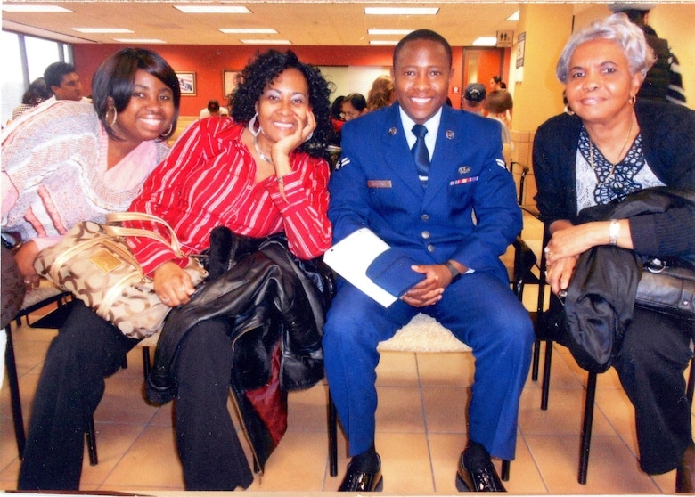 Then U.S. Air Force Airman 1st Class Tinashe Machona, assigned to the 116th Air Control Wing, poses for a photograph with co-workers anticipating his Oath of Allegiance, during a citizenship ceremony in Atlanta, Ga., Jan. 12, 2012. Machona worked as an administrative assistant at a real estate law firm in Tucker, Ga. (Courtesy photo, 2nd Lt. Tinashe Machona)