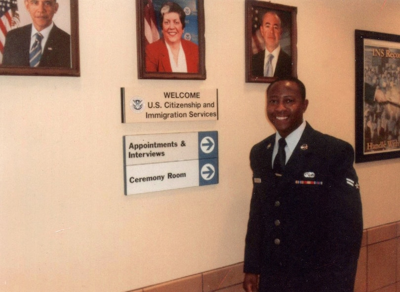 Then U.S. Air Force Airman 1st Class Tinashe Machona, assigned to the  116th Air Control Wing, poses for a photograph in the foyer a United States Citizenship and Immigration building, during a citizenship ceremony, in Atlanta, Ga., Jan. 12, 2012. Machona expedited his U.S. Citizenship after joining the U.S. Military. (Courtesy photo, 2nd Lt. Tinashe Machona)