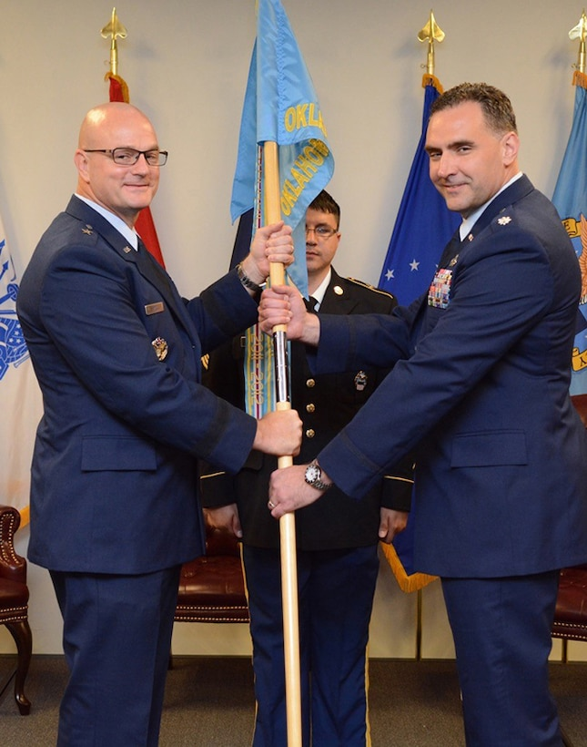 Air Force Lt. Col. James Malec, right, assumes command of Defense Logistics Agency at Oklahoma City from Air Force Col. Kenton Ruthardt. Former DLA Aviation Commander Air Force Brig. Gen. Allan Day, left, officiated the ceremony held at the Tinker Aerospace Complex, Tinker Air Force Base, Oklahoma, June 23, 2017.