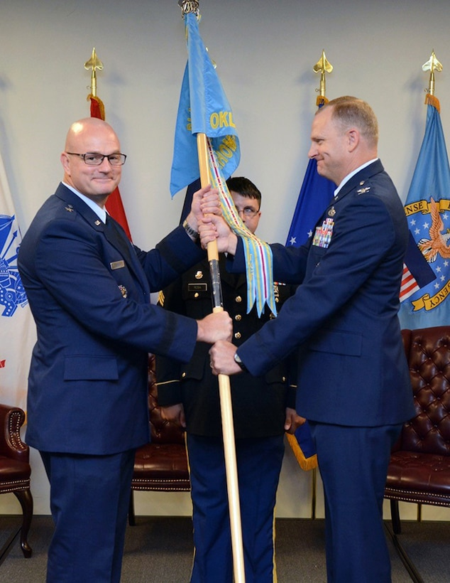 Air Force Col. Kenton Ruthardt, right, relinquishes command of Defense Logistics Agency at Oklahoma City to Air Force Lt. Col. James Malec. Former DLA Aviation Commander Air Force Brig. Gen. Allan Day, left, officiated the ceremony held at the Tinker Aerospace Complex, Tinker Air Force Base, Oklahoma, June 23, 2017.