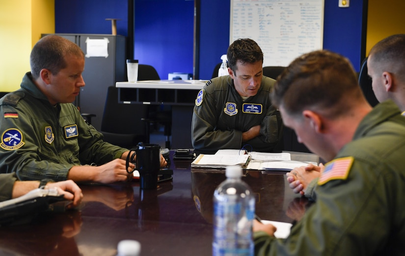 Aircrew members assigned to the 14th and 15th Airlift Squadrons, participating in the foreign exchange pilot program, discuss mission details prior to a flight here June 26, 2017. The program strives to promote mutual understanding and trust, enhance interoperability, strengthen air force to air force ties, and develop long-term professional and personal relationships between partnered countries.