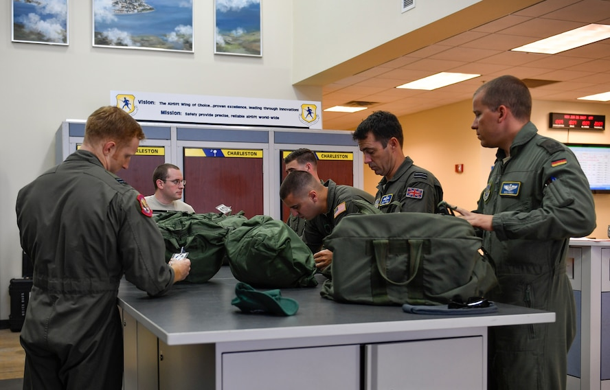 Pilots participating in the foreign exchange program and aircrew members from the 14th Airlift Squadron, inspect flight operational equipment prior to a mission flight here June 26, 2017. The focus of the program is cross-training and cross-operation aspects that provide insight for foreign nationals learning U.S. Air Force procedures and to provide additional understanding of the different ways our partner nations operate.