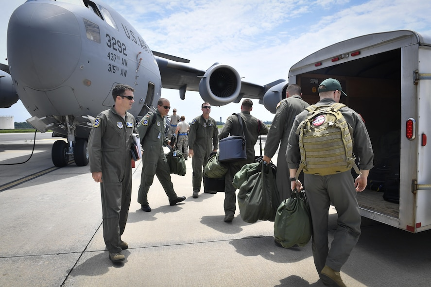 Pilots from the foreign exchange program and aircrew from the 14th Airlift Squadron, grab their flight equipment and prepare to load onto a C-17 Globemaster III aircraft here, June 26, 2017. The program strives to promote mutual understanding and trust, enhance interoperability, strengthen air force to air force ties and develop long-term professional and personal relationships.