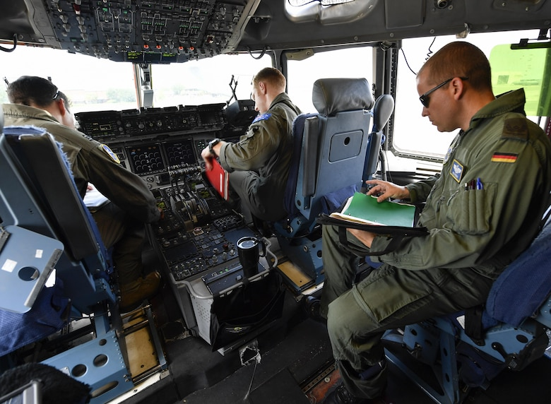 Aircrew members, assigned to the 14th and 15th Airlift Squadrons, participating in the foreign exchange pilot program discuss mission details prior to a flight here June 26, 2017. The program strives to promote mutual understanding and trust, enhance interoperability, strengthen air force to air force ties, and develop long-term professional and personal relationships between partnered countries.
