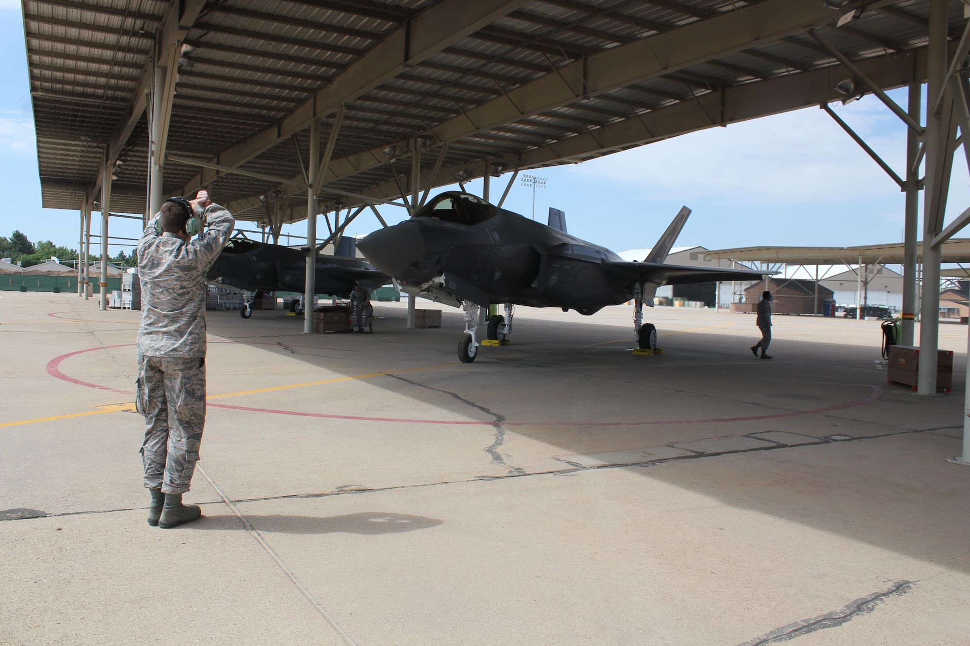 Airman 1st Class Matthew Clark with the 34th Aircraft Maintenance Unit directs the pilot who flew the 388th Fighter Wing's 24th aircraft assigned to the 34th Fighter Squadron / 34th AMU June 21. The 24th aircraft is significant because it completes the first full F-35A squadron at an operational unit. (U.S. Air Force photo/Donovan K Potter)