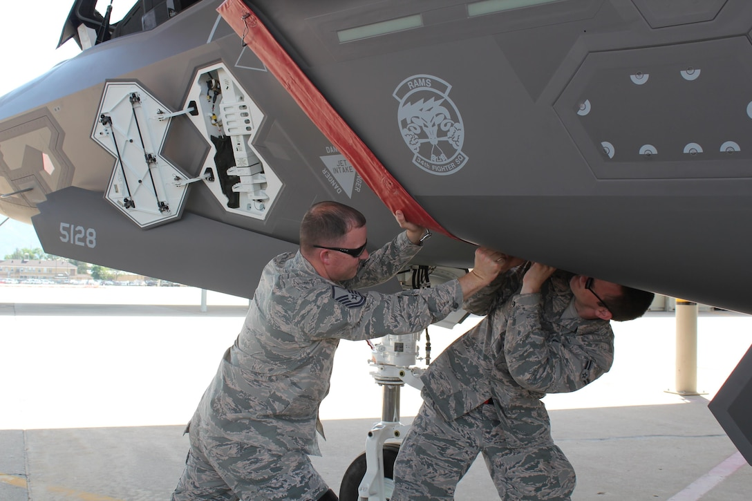 Master Sgt. Rawleigh Smith and Airman 1st Class Matthew Clark, both with the 34th Aircraft Maintenance Unit, stretch the engine cover across the 388th Fighter Wing's 24th aircraft assigned to the 34th Fighter Squadron / 34th AMU Wednesday. The 24th aircraft is significant because it completes the first full F-35A squadron at an operational unit. (U.S. Air Force photo/Donovan K Potter)