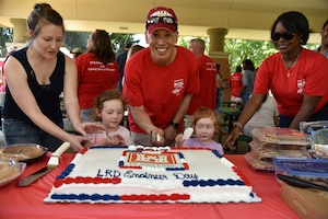 Brig. Gen. Toy cuts the cake with the two youngest LRD members at the 2017 LRD Engineer Day Picnic at Lunken Airfield in Cincinnati, Ohio.