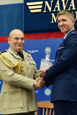 Air Chief Marshal Stuart Peach, Chief of the Defence Staff of the United Kingdom is presented with a gift by the combat systems officer class 17-11 class leader 2nd Lt. David Breeze during the graduation ceremony held inside the Naval Aviation Museum, Naval Air Station Pensacola, Florida., June 23, 2017.