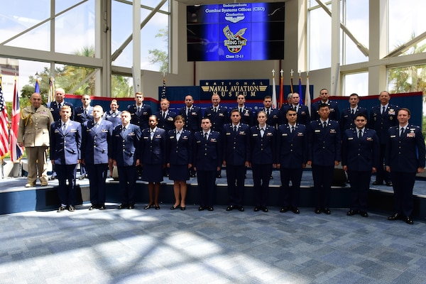 Air Chief Marshal Stuart Peach, Chief of the Defence Staff of the United Kingdom, Col. Joel Carey, 12th Flying Training Wing commander, Col. John Edwards, 479th Flying Training Group commander and Combat Systems Officer Class 17-11 pose for a group photo inside the Naval Aviation Museum, Naval Air Station Pensacola, Florida, June 23, 2017.