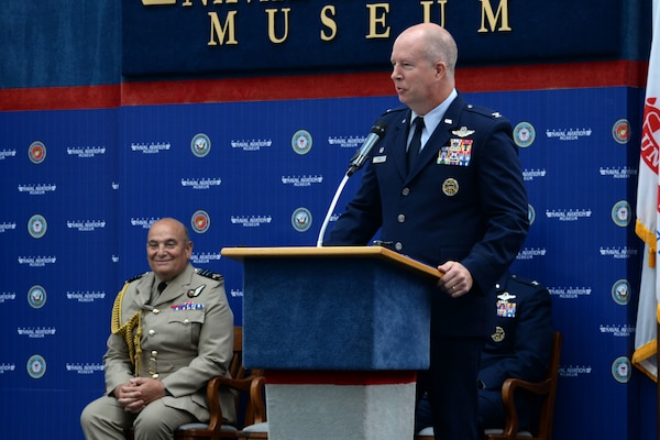 Col. Joel Carey, 12th Flying Training Wing commander provides closing comments as guest speaker while Air Chief Marshal Stuart Peach, Chief of the Defence Staff of the United Kingdom looks on during the Combat Systems Officer graduation, inside the National Naval Aviation Museum at Naval Air Station Pensacola, Florida, June 23, 2017.