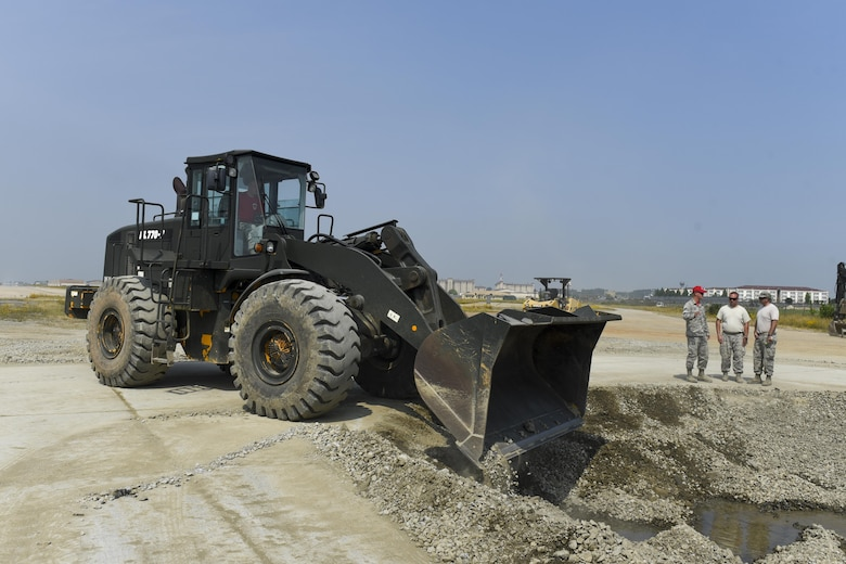 U.S. Air Force Senior Airman Robert Mcintosh, 8th Civil Engineering Squadron pavement and construction journeyman, pushes gravel into a crater using a loader June 23, 2017, Kunsan Air Base, Republic of Korea. The 8th Civil Engineering Squadron participated in airfield damage repair training as part of the final Exercise Silver Flag training held at Kunsan. U.S. Air Forces Pacific will now focus on ensuring Airmen have their three-year Silver Flag currency, prior to arriving on the Korean Peninsula, instead of conducting the training here. (U.S. Air Force photo by Senior Airman Michael Hunsaker/Released)