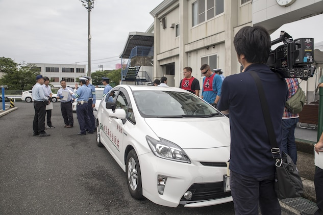 Local Japanese media record video during a free driving class held for Marine Corps Air Station Iwakuni residents in Iwakuni City, Japan, June 28, 2017. The event was the first of its kind held in Iwakuni City. Twenty station residents were invited to take part in the short educational workshop aimed to decrease the number of traffic accidents and violations caused by station residents. (U.S. Marine Corps photo by Lance Cpl. Carlos Jimenez)
