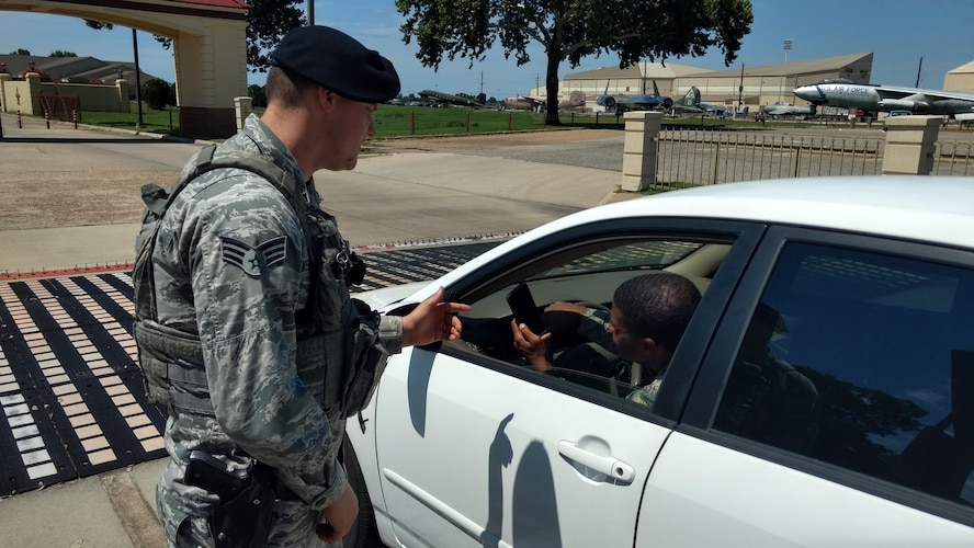 An Airman with the 2nd Security Forces Squadron speaks to a motorist at Barksdale Air Force Base, La., June 16, 2017. While smartphones have introduced a huge amount of convenience into our day-to-day routines, they have also introduced a new world of dangers being considered a major distraction for drivers. (U.S. Air Force Photo/ Nevardo Cayemitte)