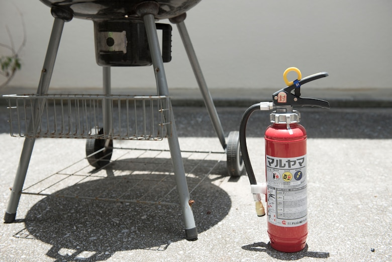 A fire extinguisher sits next to a grill June 28, 2017, at Kadena Air Base, Japan. Maintaining a fire extinguisher is especially important to help control a fire in the event of an emergency. (U.S Air Force photo by Senior Airman Quay Drawdy)