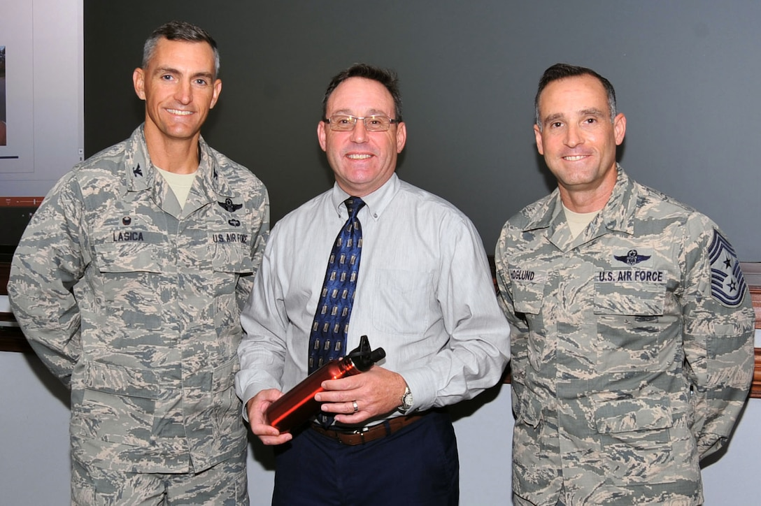 "Chris Thompson, 20th Operations Group (OG) resource advisor, center, is recognized as the Shaw ""Weasel of the Week"" by Col. Daniel Lasica, 20th Fighter Wing (FW) commander, left, and Chief Master Sgt. Daniel Hoglund, 20th FW command chief, at Shaw Air Force Base, S.C., June 28, 2017. Thompson received recognition for his efforts in acquiring resources for 20th OG Airmen to improve their work efficiency. (U.S. Air Force photo by Airman 1st Class Kathryn R.C. Reaves)"