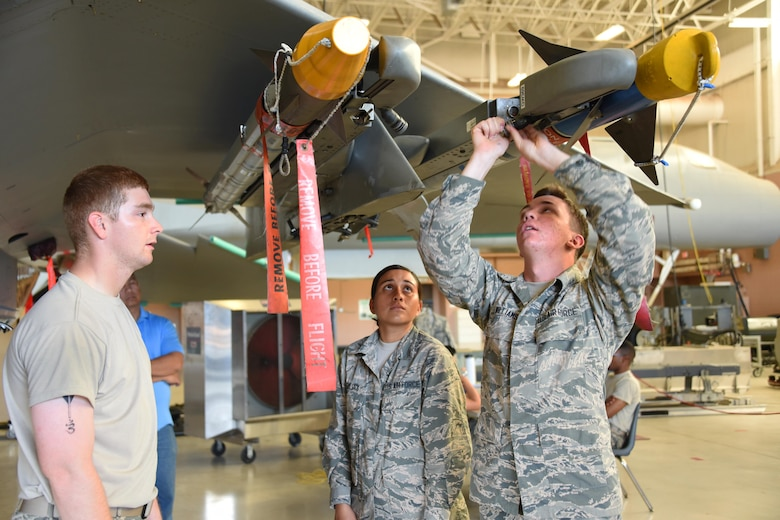 Airmen Bradd Hammond, Tyana Haylock and Anthony Williams, 363rd Training Squadron F-15 Eagle aircraft armament systems apprentice students perform functional checks of launch and suspension systems at Sheppard Air Force Base, Texas. Students learn to maintain launch and release devices and also load munitions onto them. (U.S. Air Force photo/Liz H. Colunga)
