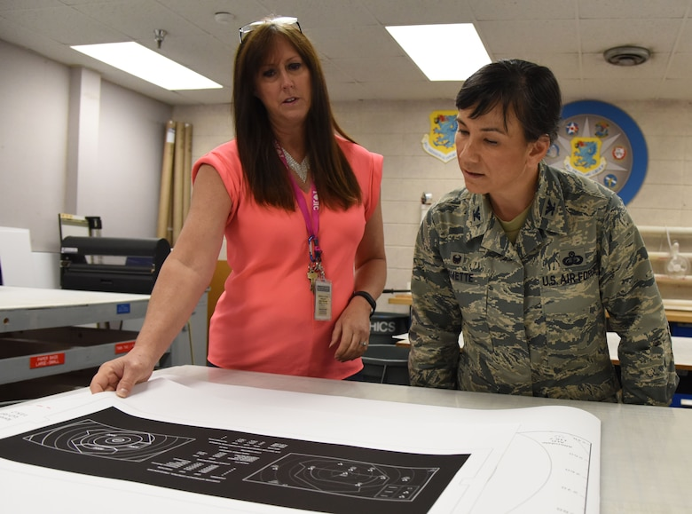 Michele Keller, 81st Training Wing public affairs graphic illustrator, shows Col. Debra Lovette, 81st TRW commander, an example of a graphic illustration at Wall Studio during a Wing Staff Agency orientation tour June 27, 2017, on Keesler Air Force Base, Miss. The tour familiarized Lovette with the Wing Staff Agency mission, operations and personnel. (U.S. Air Force photo by Kemberly Groue)