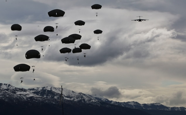 U.S. Army Paratroopers with the 4th Infantry Brigade Combat Team Airborne, 25th Infantry Division jump from a C-17 during an airborne operation at Malemute Drop Zone, Joint Base Elemendorf-Richardson, Alaska, April 5, 2016.  The realistic training provides an opportunity for mobility Airmen assigned to the 732nd Air Mobility Squadron to interact with ground-force elements and strengthen the joint relationship between Air Mobility Command and the U.S. Army. (U.S. Army photo by Staff Sgt. Brian Ragin)