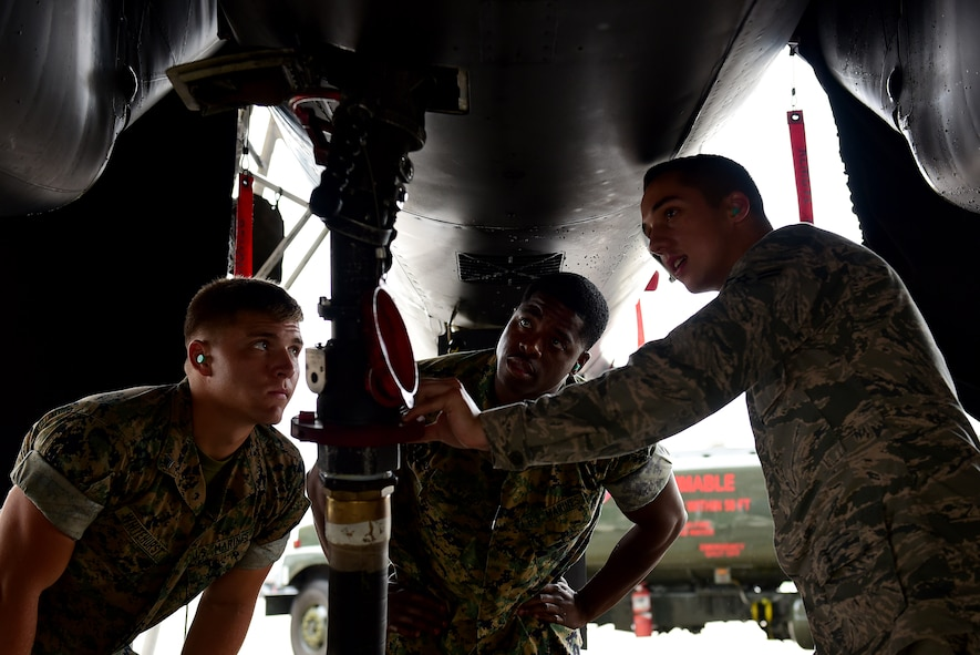 U.S. Marine Corps Lance Cpl. Austin Whitehurst, Marine Wing Support Squadron 271 bulk fuel specialist (left), Staff Sergeant David Alston, MWSS 271 platoon sergeant (middle), and Airman 1st Class Scott Plante Jr., 4th Logistics Readiness Squadron fuels specialist (right), refuel an F-15E Strike Eagle, June 22, 2017, at Seymour Johnson Air Force Base, North Carolina. Airmen trained Marines in a two-day joint training exercise to familiarize the Marines with the R-11 aircraft refueler before their deployment to Morón Air Base, Spain. (U.S. Air Force photo by Airman 1st Class Kenneth Boyton)