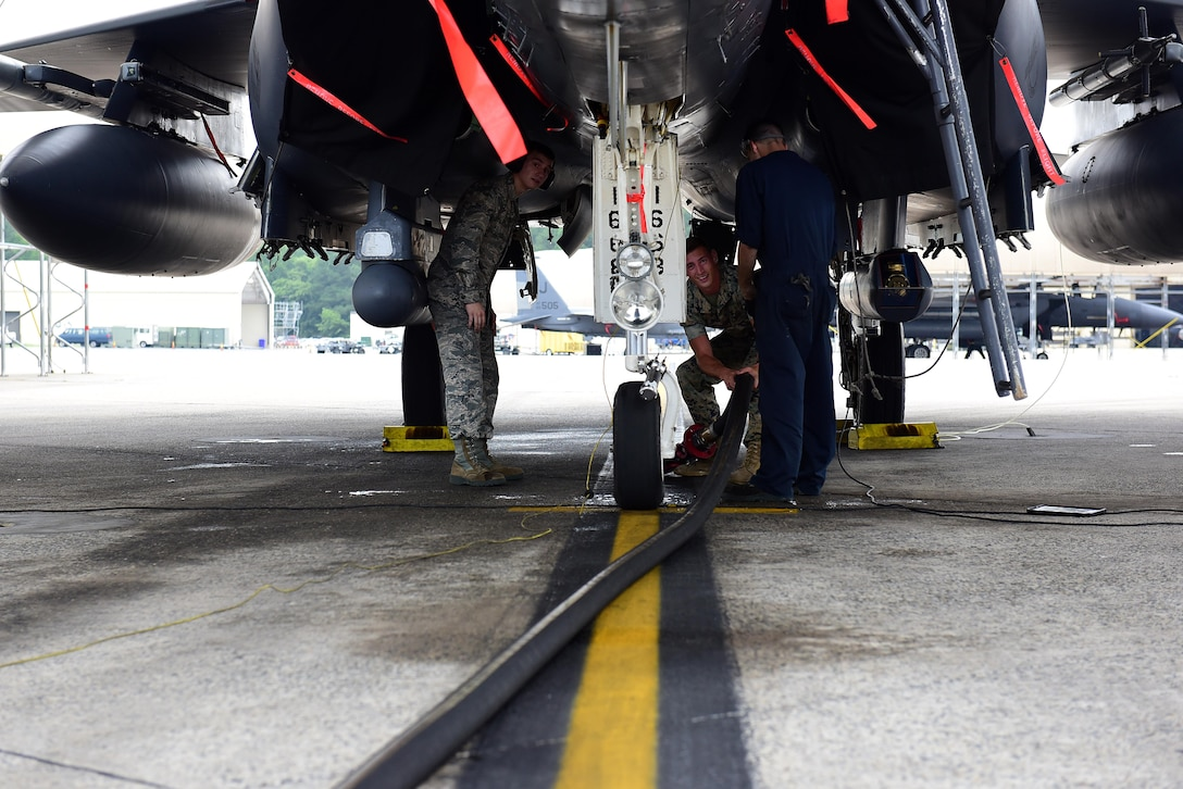 Airman Bryan Roy, 4th Logistics Readiness Squadron fuels specialist, and U.S. Marine Corps Cpl. Andrew Morris, Marine Wing Support Squadron 271 bulk fuel specialist, prepare to attach a fuel line to an F-15E Strike Eagle for refueling, June 22, 2017, at Seymour Johnson Air Force Base, North Carolina. The Marines received hands-on training with R-11 aircraft refueling vehicles before deploying to Morón Air Base, Spain. (U.S. Air Force photo by Airman 1st Class Kenneth Boyton)