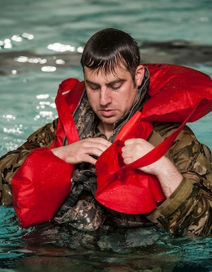 Staff Sgt. Daniel Vehslage, 54th Helicopter Squadron special missions aviator, secures a flotation device during underwater egress survival training at Minot Air Force Base, N.D., June 22, 2017. During the training, the 54th HS Airmen learned how to escape a simulated helicopter crash and properly use common rescue devices. (U.S. Air Force photo by Airman 1st Class Jonathan McElderry)