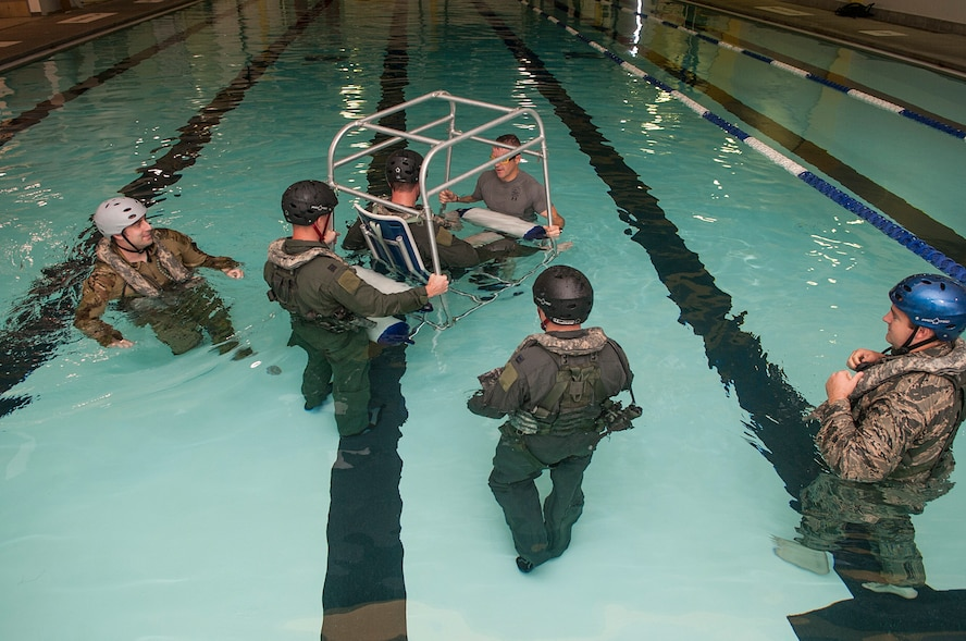 Members of the 54th Helicopter Squadron go through underwater egress survival training at Minot Air Force Base, N.D., June 22, 2017. The shallow water egress trainer allows Airmen to practice escape procedures during a simulated helicopter crash. (U.S. Air Force photo by Airman 1st Class Jonathan McElderry)