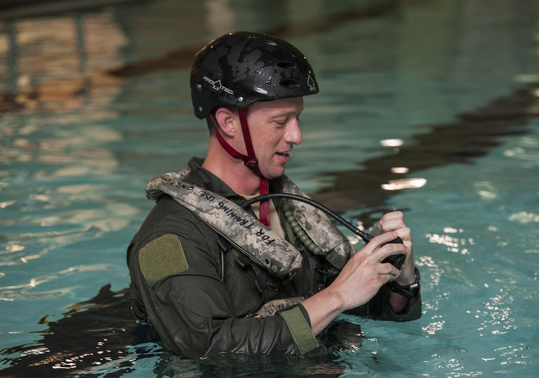 Master Sgt. David Grabher, 54th Helicopter Squadron flight engineer, tests safety equipment at Minot Air Force Base, N.D., June 22, 2017. Underwater egress survival training prepares Airmen to escape during a potential crash into water. (U.S. Air Force photo by Airman 1st Class Jonathan McElderry)